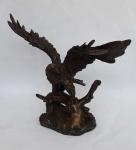 Escultura em bronze maciço representando Águia sobre tronco ricamente detalhada e cinzelada com destaque para a representação das penas na parte superior e inferior das assas, peça de coleção medindo 21 cm de altura.